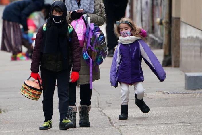 FILE PHOTO: A child skips to school at PS 361 on the first day of a return to class during the coronavirus disease (COVID-19) pandemic in the Manhattan borough of New York City