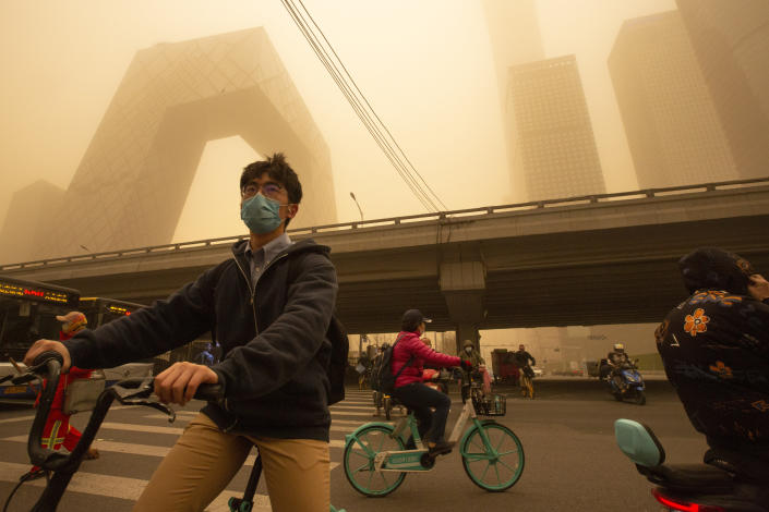 People ride bicycles across an intersection amid a sandstorm during the morning rush hour in the central business district in Beijing, Monday, March 15, 2021. The sandstorm brought a tinted haze to Beijing's skies and sent air quality indices soaring on Monday. (AP Photo/Mark Schiefelbein)