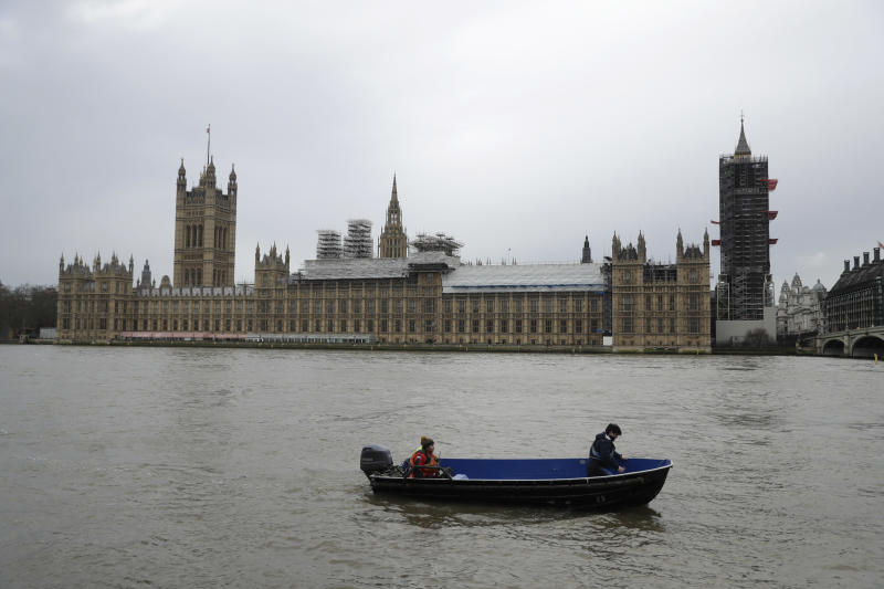 FILE - In this Wednesday, Jan. 31, 2018 file photo, people aboard a boat make way past the Houses of Parliament with Big Ben's clock tower, the Elizabeth Tower covered in scaffolding for repairs in London. British lawmakers on Thursday July 18, 2019, put a substantial roadblock in the path of any attempt by a Brexit-backing prime minister to take the country out of the European Union without a divorce deal. (AP Photo/Matt Dunham, File)