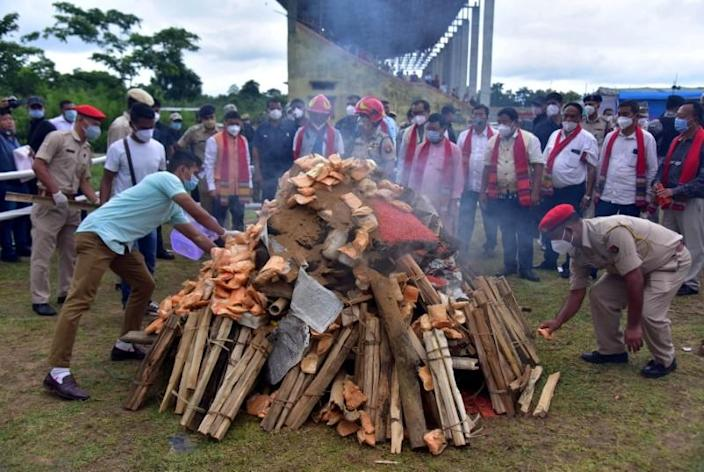 Assam Police personnel burn seized drugs during a ceremony at a playground in Karbi Anglong