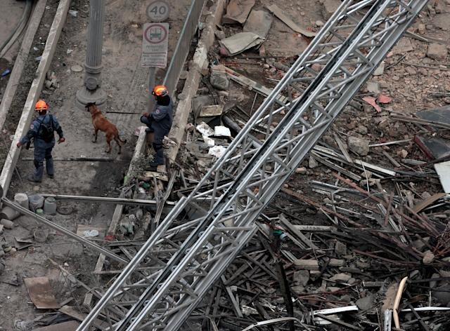 <p>Rescue workers along with sniffer dogs search for victims in a collapsed building in downtown Sao Paulo, Brazil May 1, 2018. (Photo: Leonardo Benassatto/Reuters) </p>