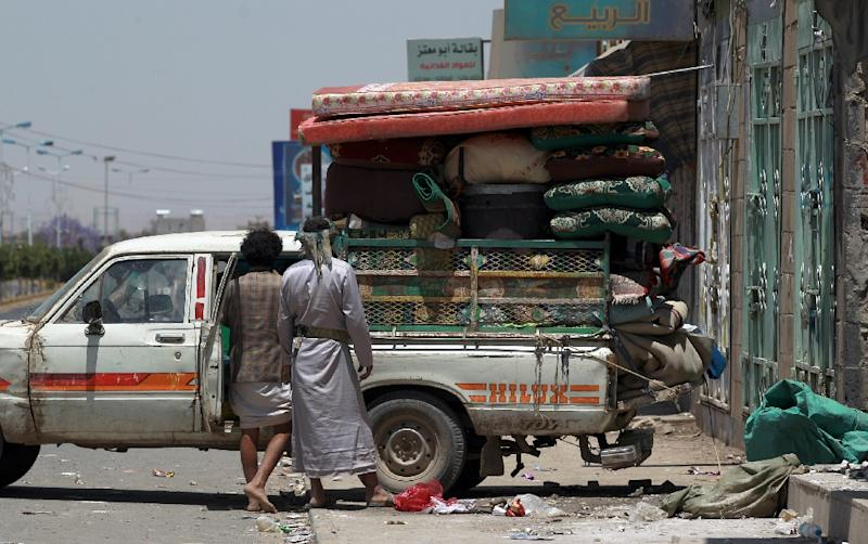 Yemenis pack their belongings into the back of a truck in Sanaa as Saudi-led coalition warplanes continue to strike Shiite Huthi militia bases across Yemen, on March 31, 2015 (AFP Photo/Mohammed Huwais)