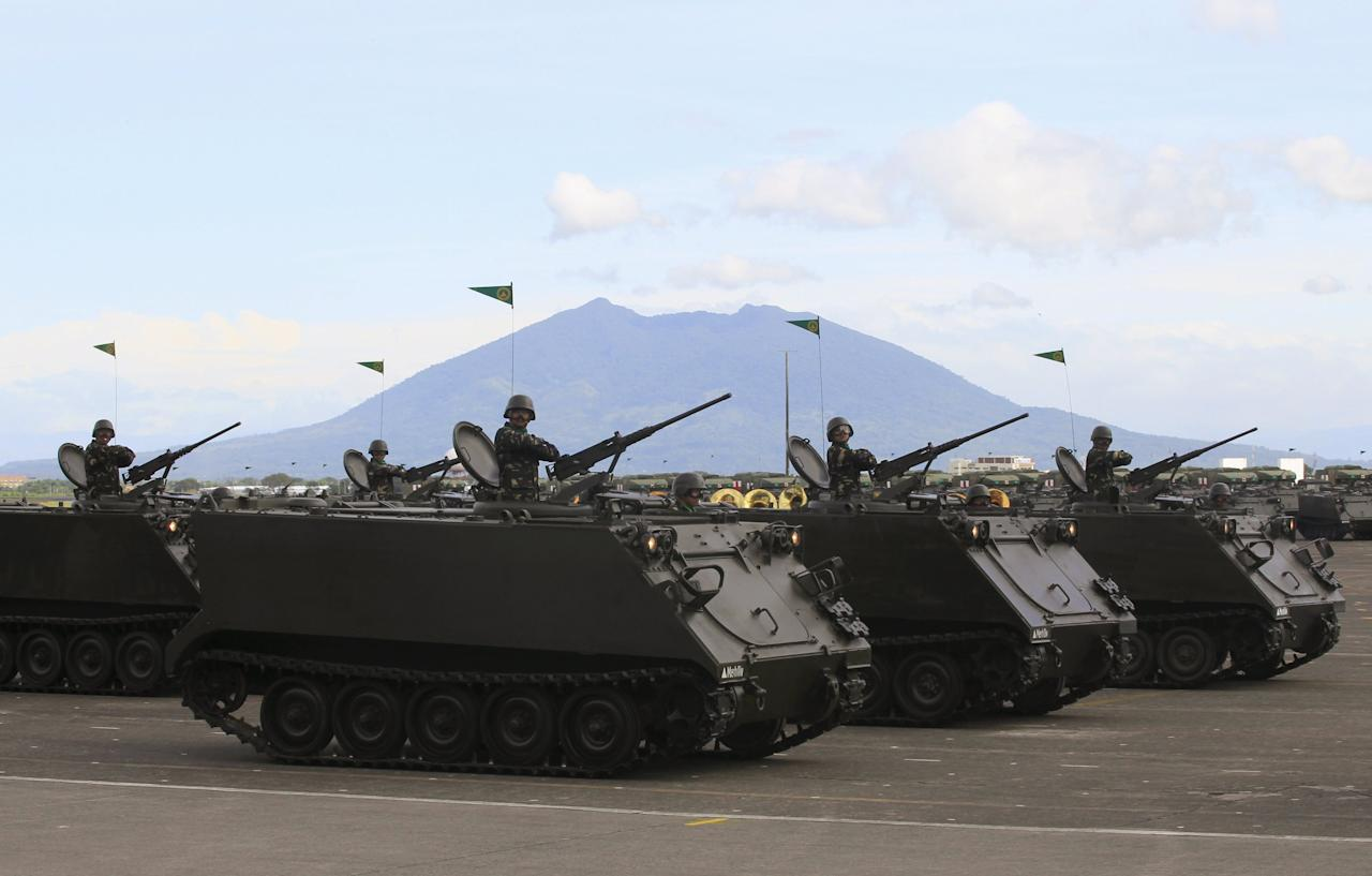 A column of tracked armoured vehicles roll ahead in a parade during the 80th founding anniversary of the Armed Forces of the Philippines held inside Clark Air Base, formerly a U.S. base, in Angeles city, Pampanga province, north of Manila December 21, 2015. Philippine President Benigno Aquino vowed on Monday to leave behind a stronger and a more capable armed forces to face maritime challenges in the South China Sea when he leaves office next year. REUTERS/Romeo Ranoco