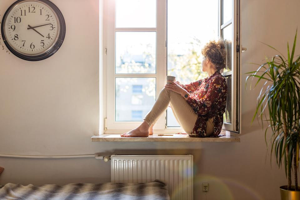 Beautiful young woman sitting at a window sill having rest