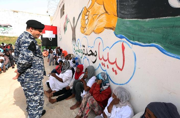 A member of the Libyan security forces stands near migrants who were hoping to reach Europe by boat as they sit at Abu Salim detention centre in the Libyan capital Tripoli on April 21, 2015 (AFP Photo/Mahmud Turkia)