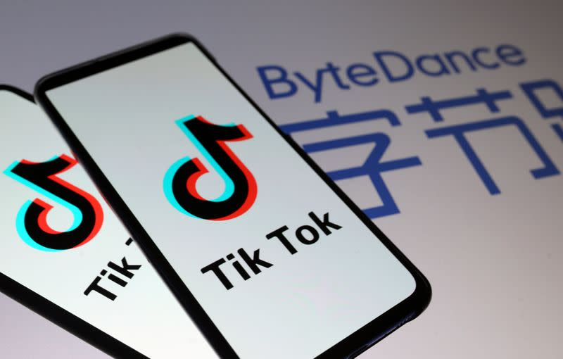 Tik Tok logos are seen on smartphones in front of displayed ByteDance logo in this illustration