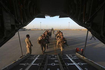U.S. Marines prepare to board a plane at the end of operations for U.S. Marines and British combat troops in Helmand
