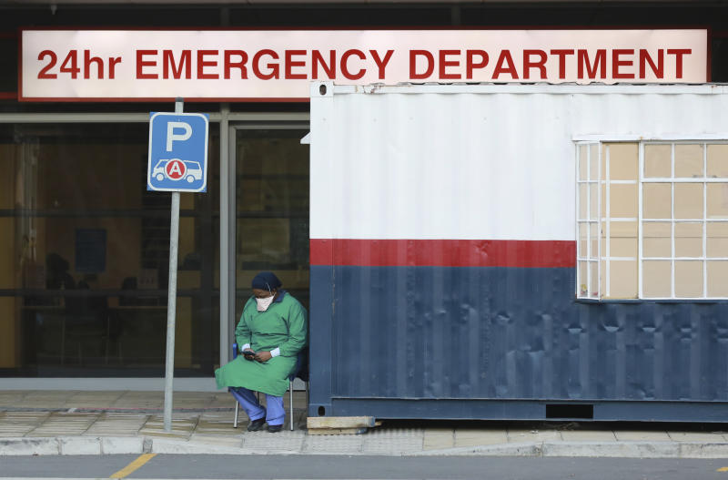FILE — In this Wednesday June 17, 2020, file photo a health worker in personal protective gear takes a break at the Netcare Christiaan Barnard Memorial Hospital in Cape Town, South Africa. South Africa's Health Minister Zwelini Mkhize said, Sunday, June 18, 2020, that the country's current surge of COVID-19 cases is expected to dramatically increase in the coming weeks and press the country's hospitals to the limit. (AP Photo/Nardus Engelbrecht/File)