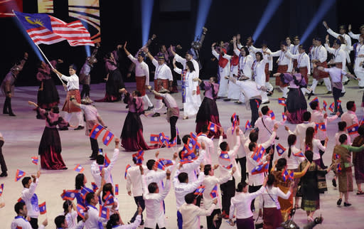 Malaysia's team hold flags during the opening ceremony of the 30th South East Asian Games at the Philippine Arena, Bulacan province, northern Philippines on Saturday, Nov. 30, 2019. (AP Photo/Aaron Favila)