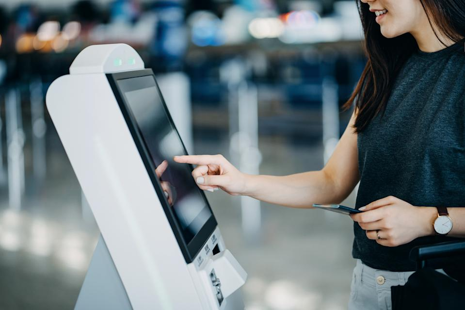 Young Asian woman travelling by plane and doing self check in at the airport using a machine