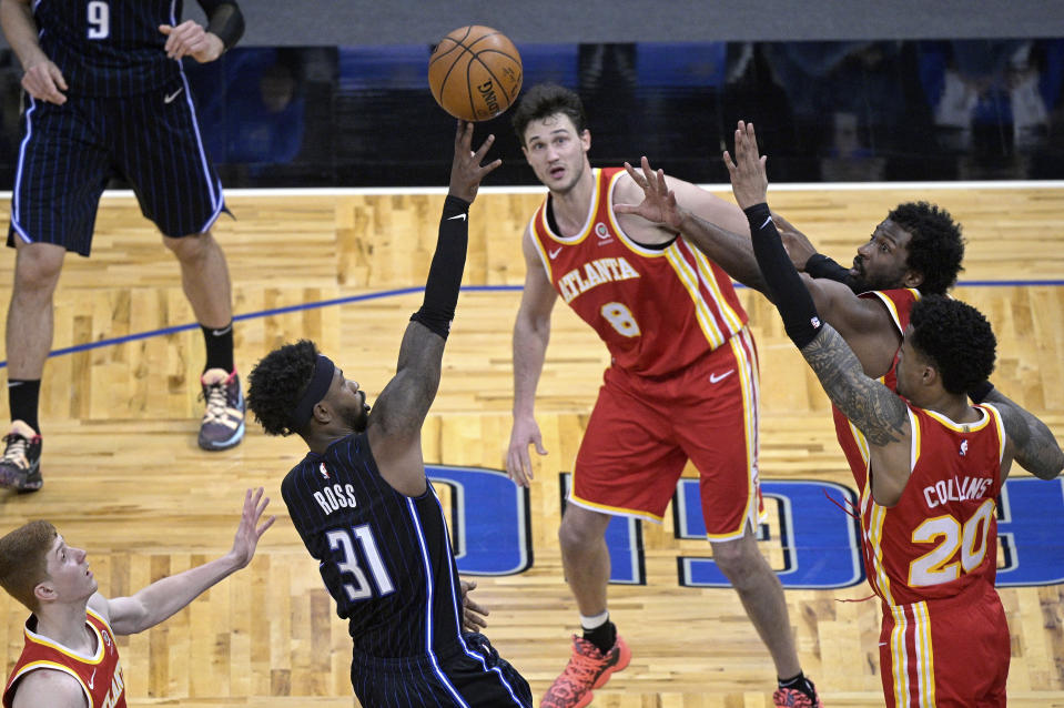 Orlando Magic guard Terrence Ross (31) shoots in the final seconds as Atlanta Hawks guard Kevin Huerter, left, forward Danilo Gallinari (8), forward Solomon Hill and forward John Collins (20) defend during the second half of an NBA basketball game Wednesday, March 3, 2021, in Orlando, Fla. (AP Photo/Phelan M. Ebenhack)