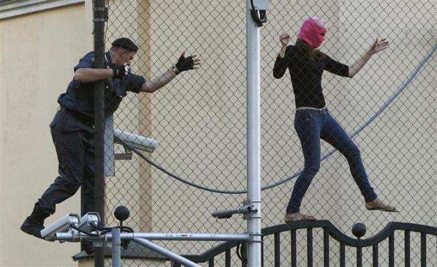 "A policeman chases a supporter of the female punk band ""Pussy Riot"" jailed members while climbing on a fence enclosing the Turkish embassy near a court building in Moscow, August 17, 2012."