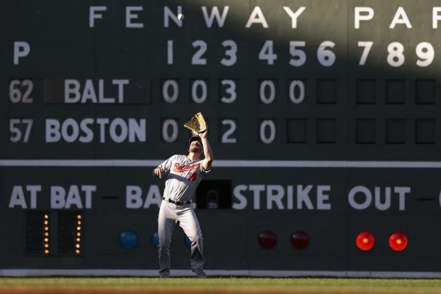 Baltimore Orioles' Trey Mancini makes the catch on the fly out by Boston Red Sox's Rafael Devers during the fifth inning of a baseball game in Boston, Sunday, Sept. 29, 2019. (AP Photo/Michael Dwyer)