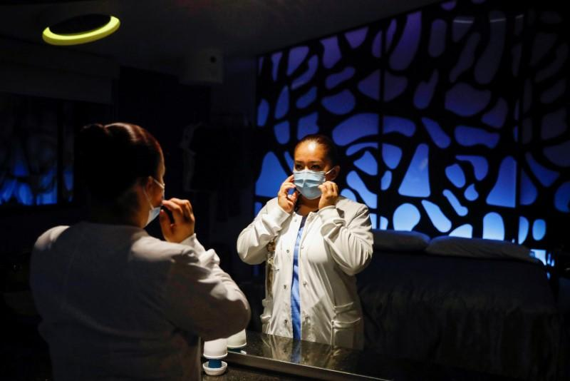 Nurse Gisela Hernandez, who has stayed away from her children for nearly two months to avoid infecting them because she feels inadequately protected, puts her face mask on before going to work, at her hotel room in Mexico City