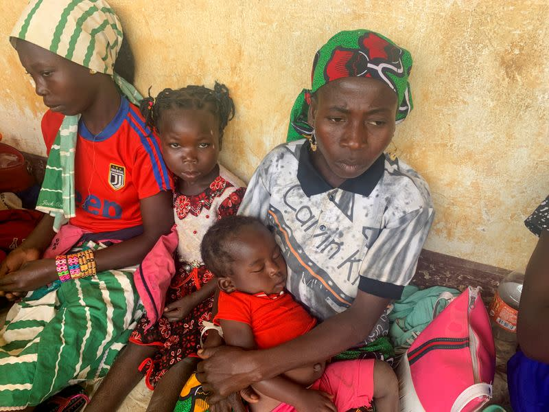 A woman who fled the violent rebellion in Central African Republic (CAR) sits with her family as they wait for their identification process in the border town of Garoua Boulai