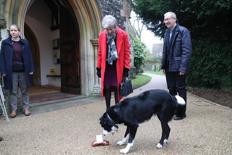 Theresa May gives a dog called Blitz a Christmas gift as she arrives with her husband Philip May to attend the morning Christmas Day service at a church near her constituency home (PA)