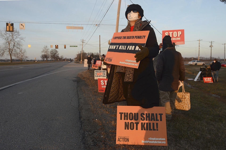 Karen Burkhart holds a sign across the road from the Federal Correctional Complex in Terre Haute, Ind., to protest the scheduled execution of Lisa Montgomery, Tuesday, Jan. 12, 2021. An appeals court granted a stay of execution Tuesday for Montgomery, convicted of killing a pregnant woman and cutting the baby from her womb in the northwest Missouri town of Skidmore in 2004. (Joseph C. Garza/The Tribune-Star via AP)