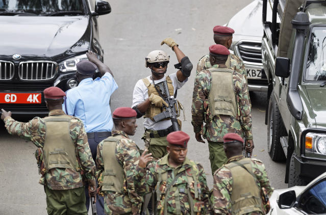 A member of Kenyan special forces, center, gestures to his colleagues to move out, at the scene of the attack Wednesday, Jan. 16, 2019 in Nairobi, Kenya. Extremists stormed a luxury hotel in Kenya's capital on Tuesday, setting off thunderous explosions and gunning down people at cafe tables in an attack claimed by Africa's deadliest Islamic militant group. (AP Photo/Ben Curtis)