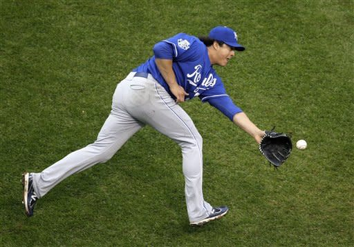 Kansas City Royals starting pitcher Luis Mendoza flips the ball to first after fielding a grounder hit by Cleveland Indians' Michael Brantley in the sixth inning of a baseball game in Cleveland on Thursday, April 26, 2012. Brantley was safe on the play. (AP Photo/Amy Sancetta)