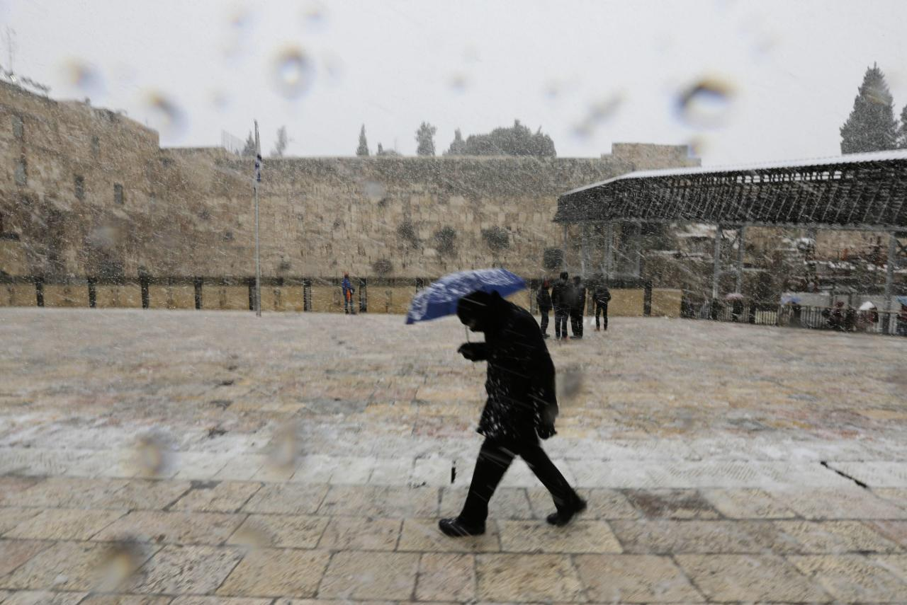 A man holding an umbrella walks as snow falls at the Western Wall in Jerusalem's Old City December 12, 2013. Snow fell in Jerusalem and parts of the occupied West Bank where schools and offices were widely closed and public transport was paused. REUTERS/Ammar Awad (JERUSALEM - Tags: RELIGION ENVIRONMENT)