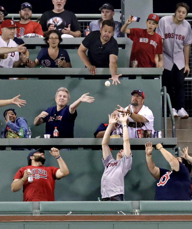 Fans try to catch the ball on a three run home run by Boston Red Sox's J.D. Martinez during the eighth inning of a baseball game against the Texas Rangers at Fenway Park in Boston, Monday, July 9, 2018. (AP Photo/Charles Krupa)
