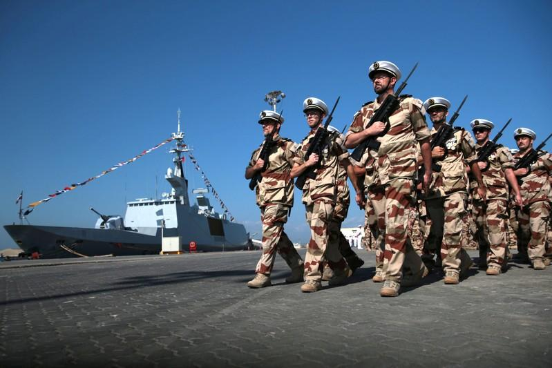 Members of the French Armed Forces march past the French frigate Courbet while taking part in a military cermony at the French Naval Base in Abu Dhabi