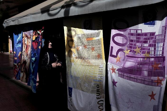 A kiosk owner stands behind towels depicting Euro banknotes hanged at his kiosk in Athens, Greece, on March 22, 2015 (AFP Photo/Angelos Tzortzinis)