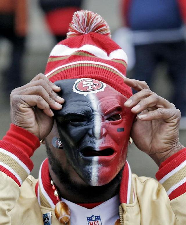 A San Francisco 49ers fan puts on a mask outside CenturyLink Field before the NFL football NFC Championship game against the Seattle Seahawks Sunday, Jan. 19, 2014, in Seattle. (AP Photo/Elaine Thompson)