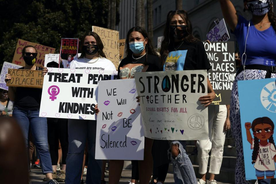 Demonstrators hold signs during a Women's March.