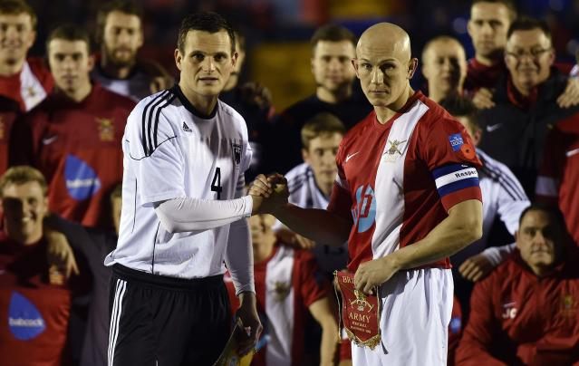 British Army soccer team captain Sergeant Keith Emmerson (R) shakes hands with his German counterpart, Bundeswehr captain Alfred Hess, at Aldershot Town FC stadium in Aldershot in south England, December 17, 2014. The two teams were playing each other in a 'Game of Truce' soccer match, commemorating 100 years since the famous peaceful interlude to fighting in World War I when members of the opposing British and German forces played a game of soccer in No Man's Land on Christmas Day 1914. REUTERS/Toby Melville (BRITAIN - Tags: SPORT SOCCER POLITICS ANNIVERSARY CONFLICT MILITARY)