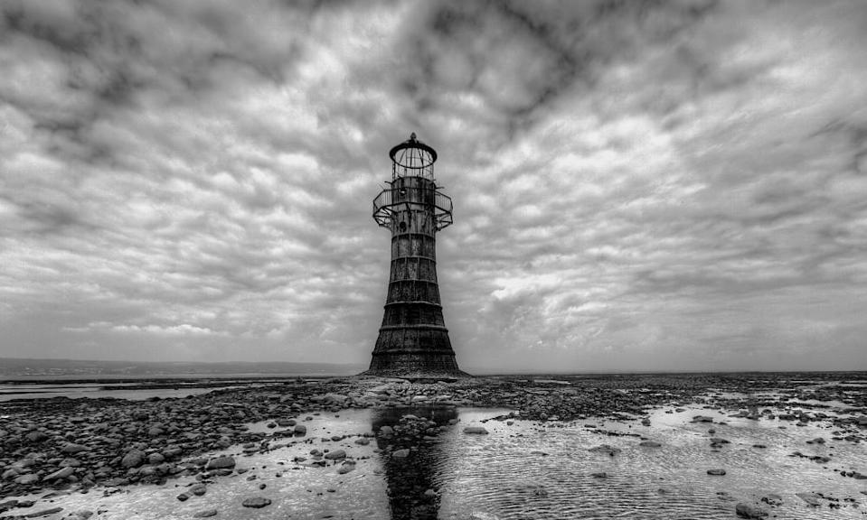 Lighthouse at Whiteford with dramatic sky black and white image