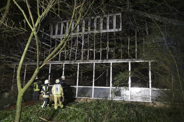 Firefighters stand in front of a burnt-out animal house at Krefeld Zoo in Germany