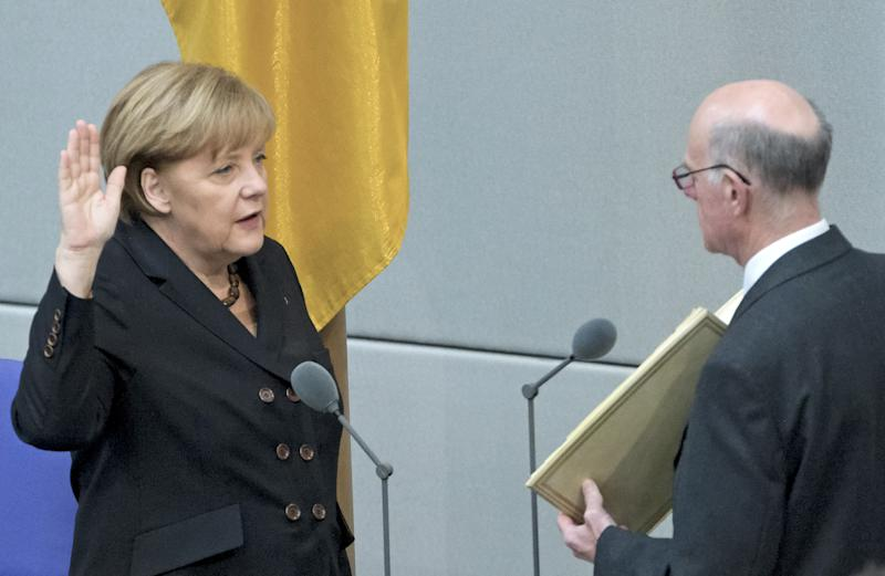 German Chancellor Angela Merkel, left, takes the oath of office by President of the Federal Parliament, Norbert Lammert during a meeting of the German federal parliament, Bundestag, in Berlin, Germany, Tuesday, Dec. 17, 2013. (AP Photo/Jens Meyer)