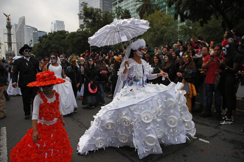 People dressed as Catrinas parade down Mexico City's iconic Reforma avenue during celebrations for the Day of the Dead in Mexico, Saturday, Oct. 26, 2019. (AP Photo/Ginnette Riquelme)