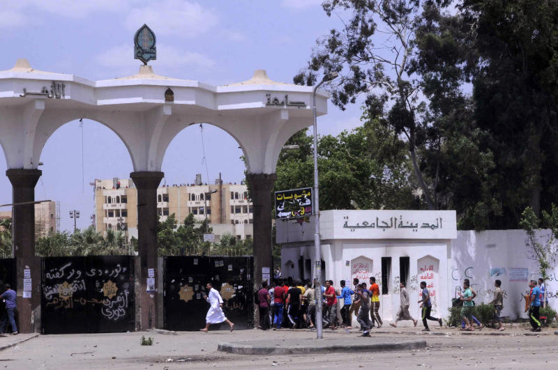 Protesters run into a student housing area of Al-Azhar University as clashes with Egyptian security forces escalate in Cairo, Egypt, Friday, May 9, 2014. Supporters of Egypt's Islamist President Mohammed Morsi continue to protest in the streets as retired Field Marshal Abdel-Fattah el-Sissi, who led last year's overthrow of Morsi, appears poised to win in the presidential election planned this month. (AP Photo/Mohammed Asad)