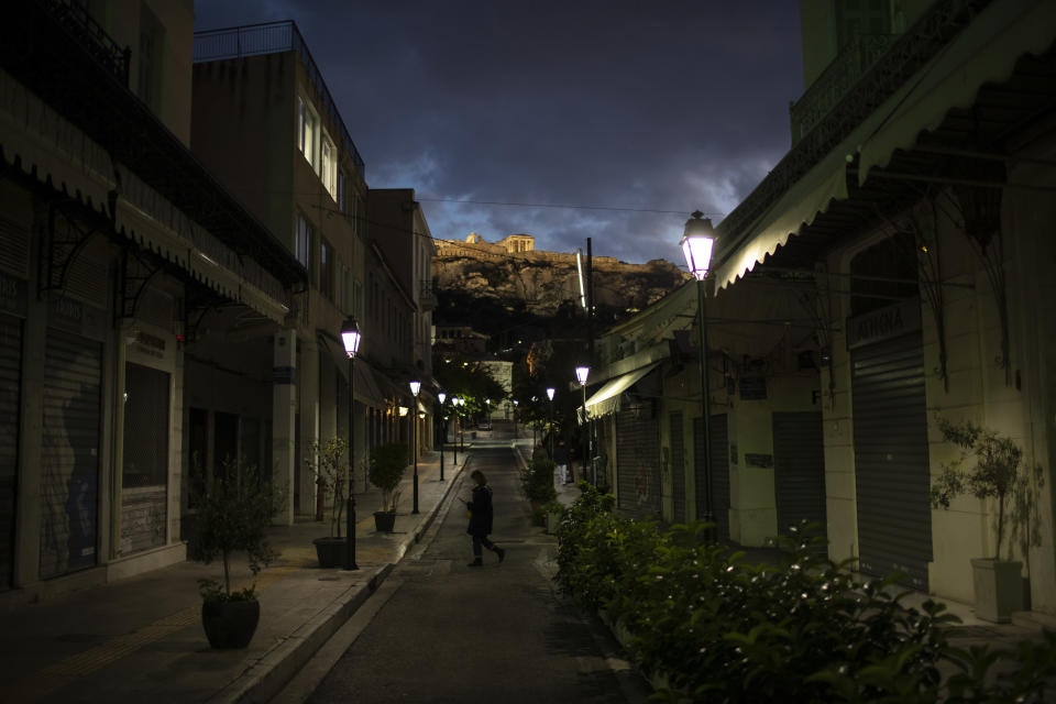 A woman walks on an empty street in the Plaka district of Athens with a part of the ancient Erechtheion temple on the Acropolis in the background, Tuesday, Nov. 24, 2020. Outbreaks of COVID-19 prompted Greece to impose two countrywide lockdowns, in the spring, keeping infection rates low, and in the fall as authorities scrambled to cope with a rampant rise in cases. (AP Photo/Petros Giannakouris)