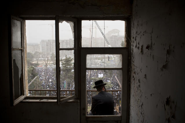 <p>An Ultra-Orthodox Jewish man watches from a balcony as hundreds of thousands of Ultra-Orthodox Jews rally in a massive show of force against plans to force them to serve in the Israeli military, blocking roads and paralyzing the city of Jerusalem, March 2, 2014. (Photo: Oded Balilty/AP) </p>