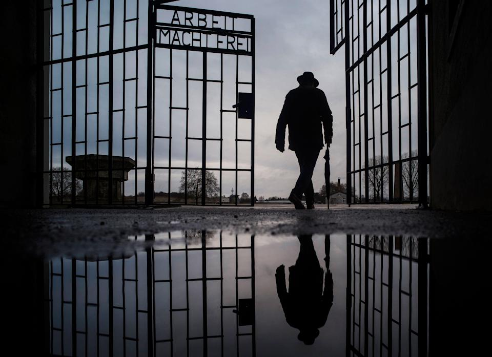 In this Sunday, Jan. 27, 2019 file photo, a man walks through the gate of the Sachsenhausen Nazi death camp with the phrase 'Arbeit macht frei' (work sets you free) during International Holocaust Remembrance Day in Oranienburg, about 18 miles north of Berlin, Germany. German prosecutors say they have charged a 100-year-old man with 3,518 counts of accessory to murder on allegations he served as an SS guard at the Nazis' Sachsenhausen concentration camp on the outskirts of Berlin.