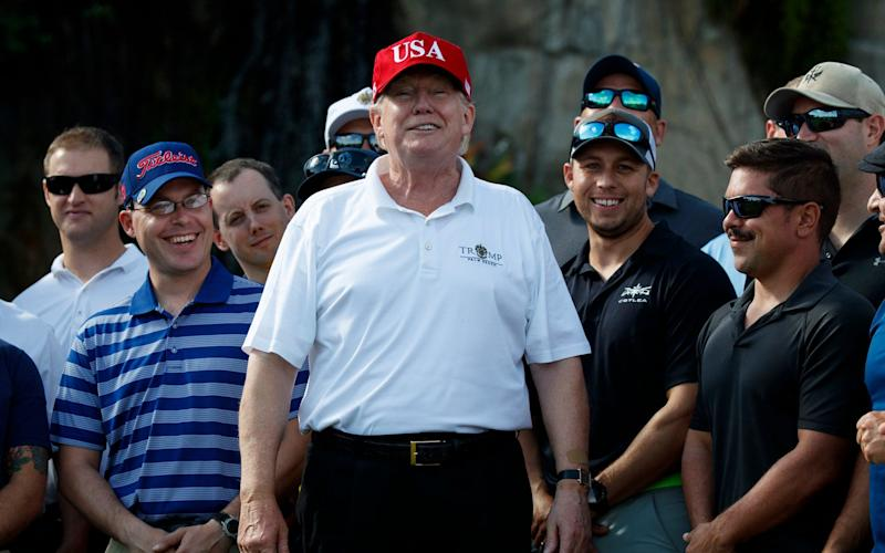 Trump smiles as he meets with members of the U.S. Coast Guard, who he invited to play golf, at Trump International Golf Club in West Palm Beach, Florida, in December - AP