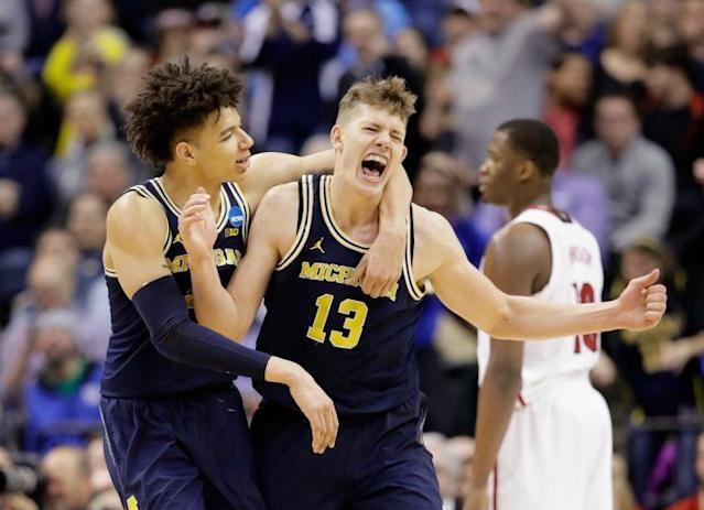 Moritz Wagner (R) celebrates a shot with D.J. Wilson in the second half of Michigan's win over Louisville on Sunday. (Getty)