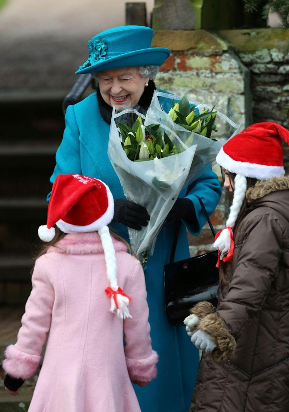 <p>Queen Elizabeth smiles as she receives flowers from young well-wishers on Christmas Day.</p>