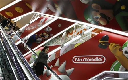 People ride an escalator past Nintendo Co advertisements at an electronics retail store in Tokyo