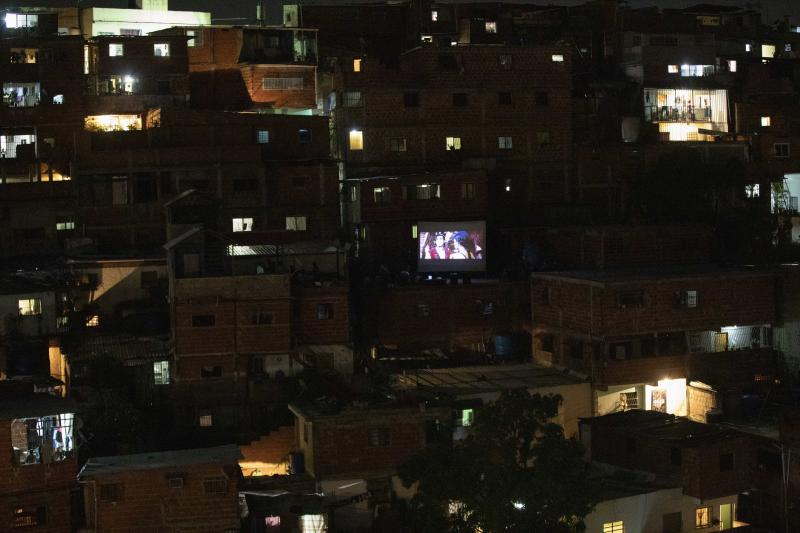 The film Aladdin is projected on a screen set up on the roof of a home, center right, in the Petare neighborhood of Caracas, Venezuela, late Monday, June 1, 2020. A neighborhood group called The Download Zone set up the movie as a free entertainment option for families cooped up since mid-March under the COVID-19 quarantine. (AP Photo/Ariana Cubillos)