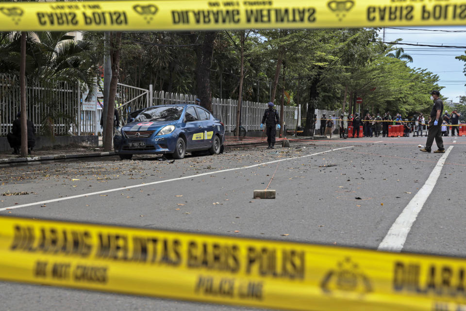 Members of the police bomb squad inspect the area around the site of Sunday's suicide bomb attack at the Sacred Heart of Jesus Cathedral in Makassar, South Sulawesi, Indonesia, Monday, March 29, 2021. Two attackers believed to be members of a militant network that pledged allegiance to the Islamic State group blew themselves up outside the packed Roman Catholic cathedral during a Palm Sunday Mass on Indonesia's Sulawesi island, wounding a number of people, police said. (AP Photo/Yusuf Wahil)