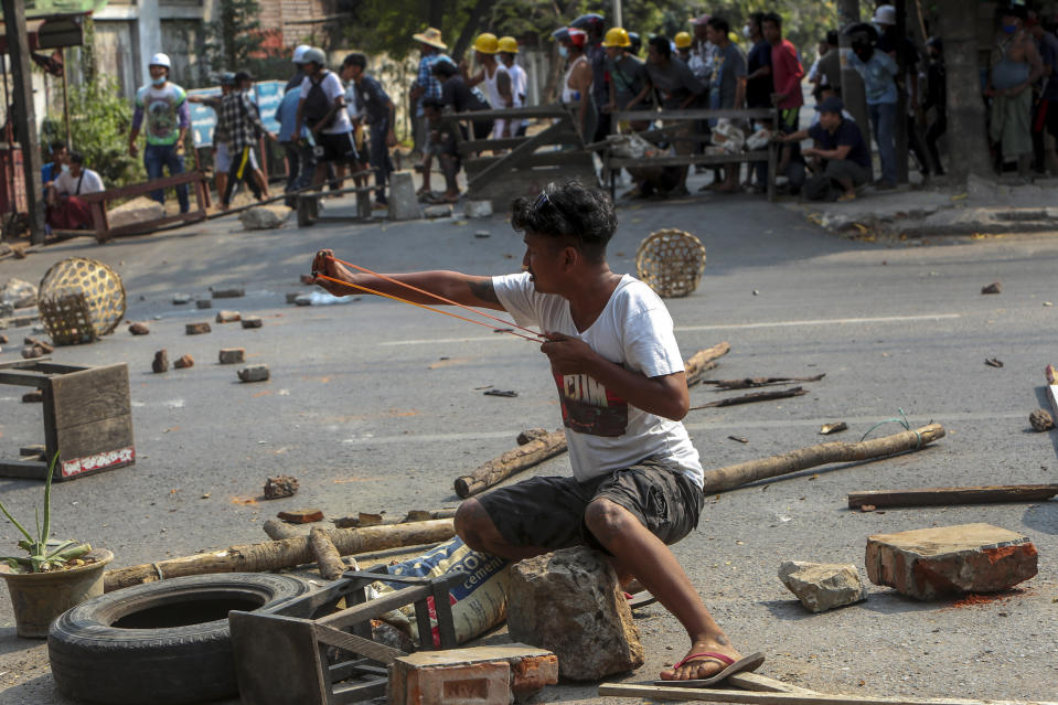 An anti-coup protester uses a sling-shot and against advancing riot policemen in Mandalay, Myanmar, Tuesday, March 2, 2021. Demonstrators in Myanmar took to the streets again on Tuesday to protest last month's seizure of power by the military, as foreign ministers from Southeast Asian countries met to discuss the political crisis. Police in Yangon, Myanmar's biggest city, used tear gas and rubber bullets against the protesters. (AP Photo)