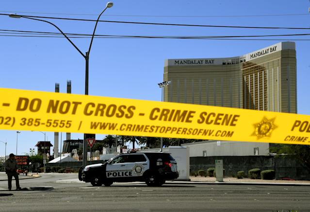 <p>Crime scene tape surrounds the Mandalay Hotel (background with shooters window damage top right) after a gunman killed dozens of people and wounded hundreds when he opened fire on a country music concert in Las Vegas, Nev. on Oct. 2, 2017. (Photo: Mark Ralston/AFP/Getty Images) </p>