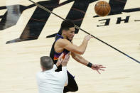 Phoenix Suns guard Devin Booker tries to save a loose ball as he collides with Denver Nuggets head coach Michael Malone during the second half of Game 2 of an NBA basketball second-round playoff series, Wednesday, June 9, 2021, in Phoenix. (AP Photo/Matt York)