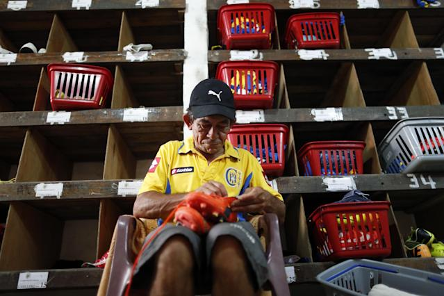 In this Oct. 18, 2014 photo, Deportivo Capiata soccer team aide Juan Abalos prepares players' shoes before a national league match against Cerro Porteno in Capiata, Paraguay. Capiata has a tiny fan base, and everything about the club is modest: its dressing room, workout room and stadium amenities. (AP Photo/Jorge Saenz)