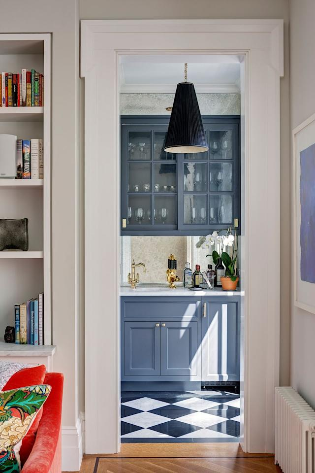 "<p>In a Greek Revival by <a href=""https://deringhall.com/architects/cwb-architects"" target=""_parent"">CWB Architects</a>, a slate-blue bar off the living area is lit up with a cone-shaped pendant light.</p>"