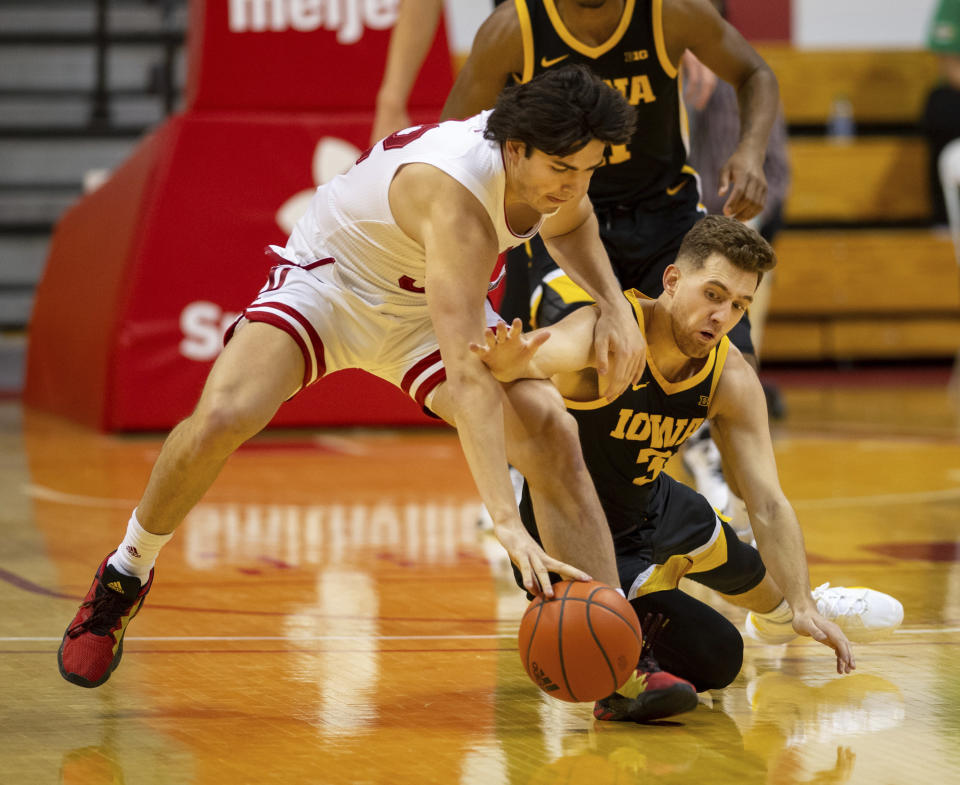 Indiana guard Trey Galloway (32), left, and Iowa guard Jordan Bohannon (3) battle for the ball during the first half of an NCAA college basketball game, Sunday, Feb. 7, 2021, in Bloomington, Ind. (AP Photo/Doug McSchooler)